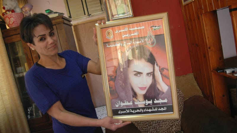 Nidal Atwan holds a poster of her daughter, Majd, after her arrest last month [Allison Deger/Al Jazeera]