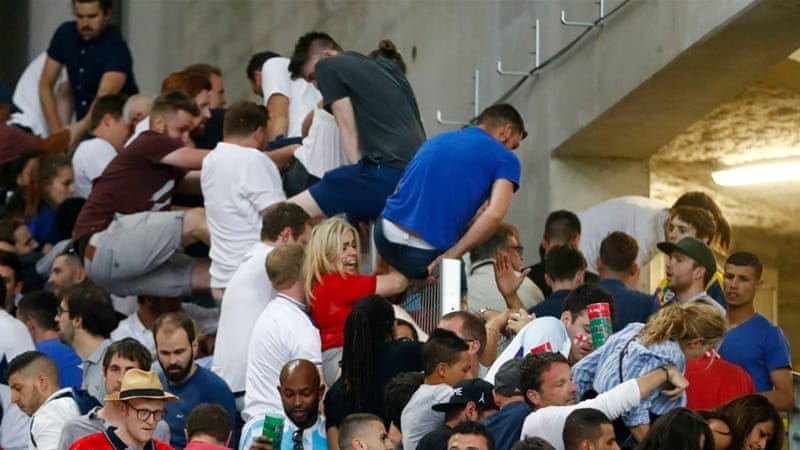 England fans climb over a fence to escape trouble in the stadium after their country's match against Russia [Kai Pfaffenbach/Reuters]