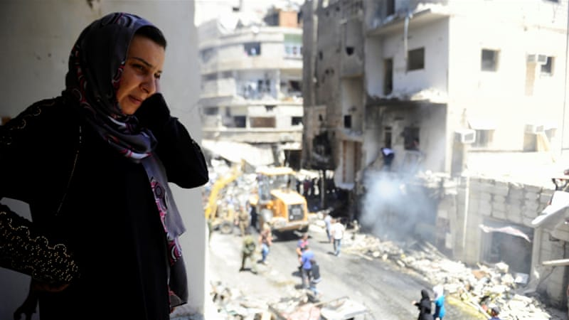 A woman inspects a damaged site after a suicide and car bomb attack in south Damascus suburb of Sayeda Zeinab, Syria [REUTERS]