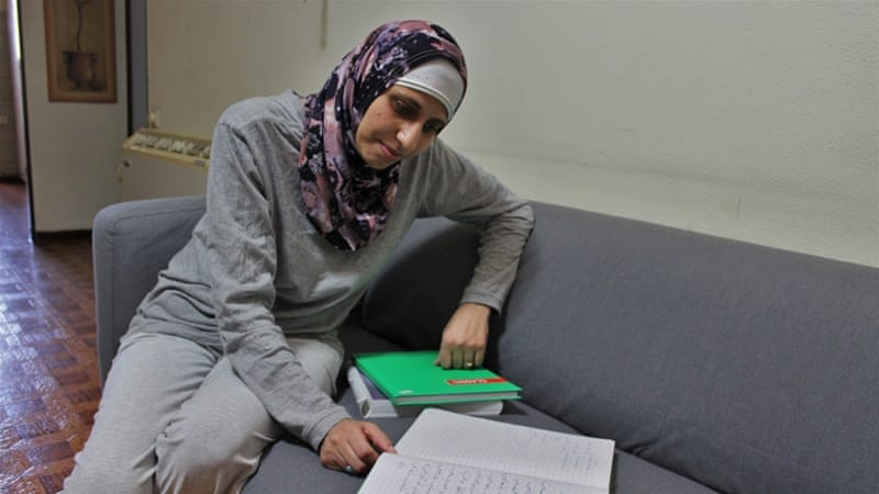 Dareen Tatour, who remains under house arrest, reads from one of her notebooks of poems [Nigel Wilson/Al Jazeera]