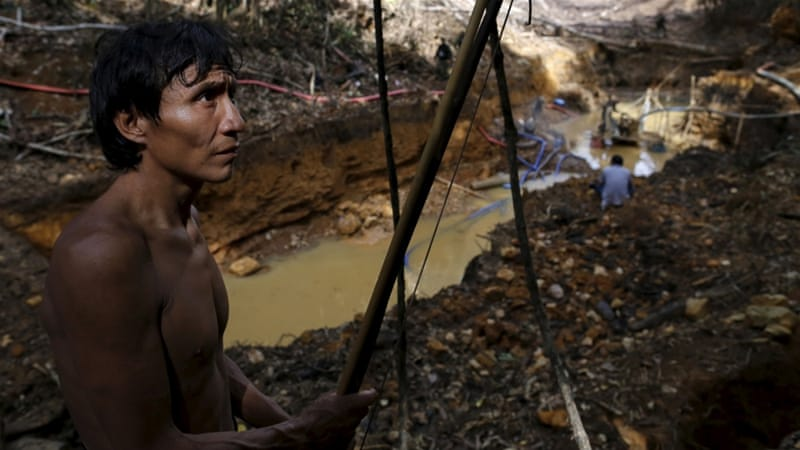 A Yanomami indian stands near an illegal gold mine during Brazil's environmental agency operation against illegal gold mining on indigenous land. [Reuters]