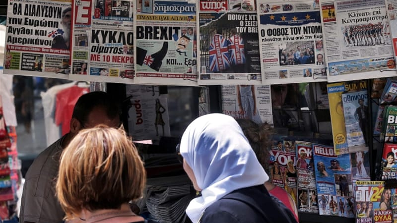 People glance at the front pages of Greek newspapers hanging on a kiosk in central Athens, Greece [EPA]