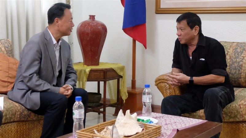 Filipino President-elect Rodrigo Duterte (right) talking to Chinese envoy Zhang Jianhua during a meeting in Davao City, southern Philippines on June 2 [EPA]
