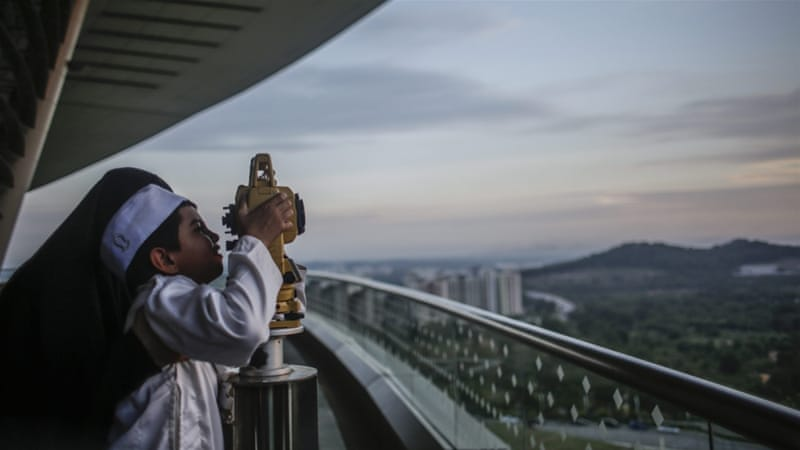 A mother holds her son to look at a theodolite to determine the sighting of the new moon to mark the start of Ramadan [Fazry Ismail/EPA]