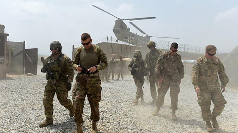 US army soldiers walk as a NATO helicopter flies overhead at coalition base in the eastern province of Nangarhar [Getty] [Getty Images]