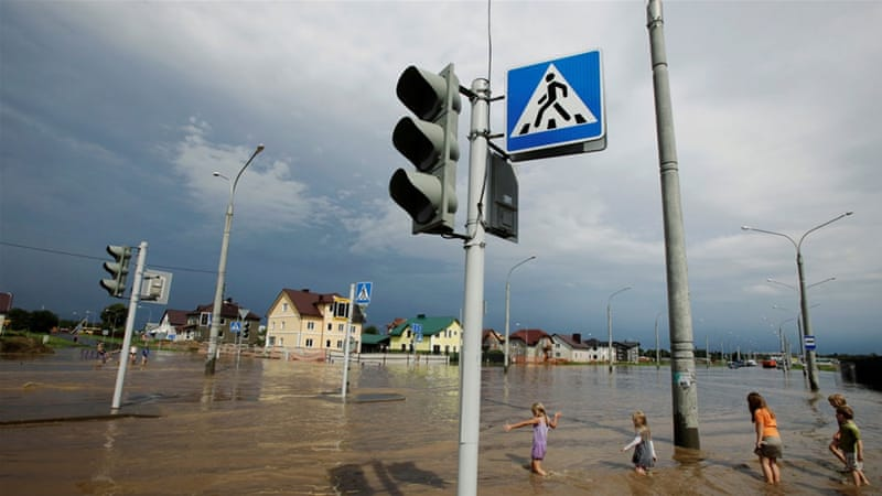 Children enjoying an impromptu paddling pool, after a thunderstorm, on a flooded street in Minsk. [Vasily Fedosenko/Reuters]