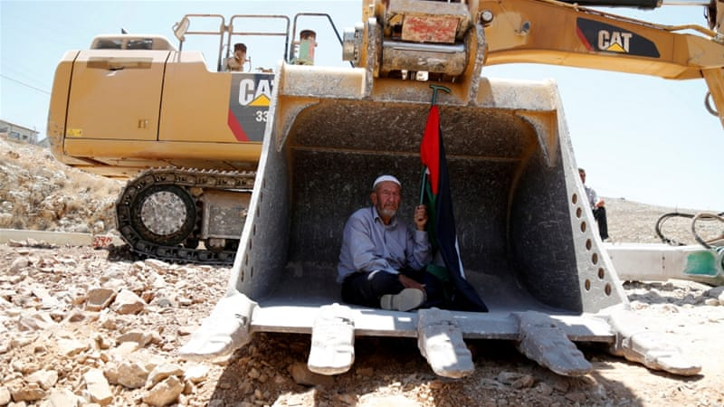 A Palestinian protests as he sits in the scoop of an Israeli excavator near Ramallah [Reuters]
