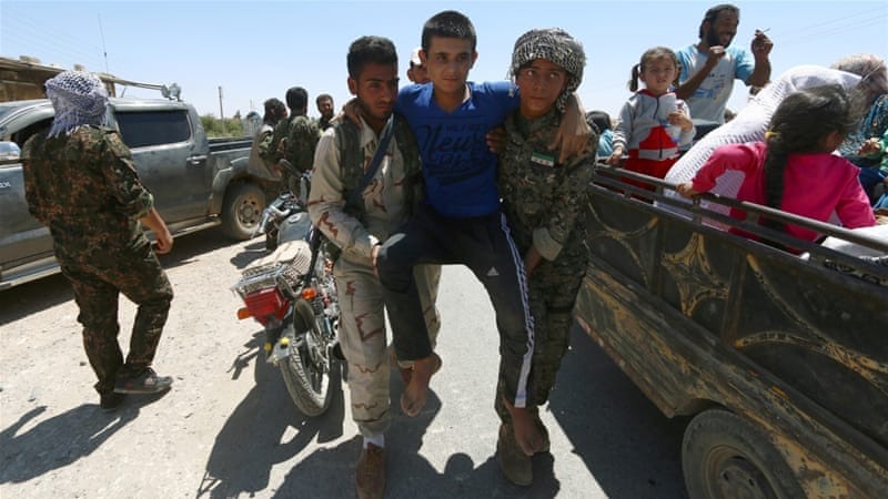 File photo from July 1 shows Syria Democratic Forces (SDF) fighters helping an injured civilian as residents evacuate from the southern districts of Manbij city. [Rodi Said/Reuters]