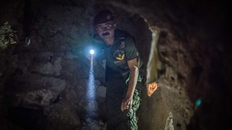 A member of Kurdish security forces in Sinjar makes his way through a tunnel dug by ISIL [John Beck/Al Jazeera]