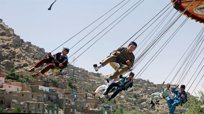 Afghan youths ride on swings during the first day of the Muslim holiday of Eid al-Fitr, in Kabul, Afghanistan [Reuters]