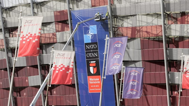 Workers place banners in preparation for the NATO summit in Warsaw, Poland [EPA]