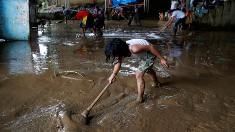 Removing mud that was brought by monsoon rains at an evacuation center in San Mateo, Rizal, Philippines.[REUTERS/Erik De Castro]