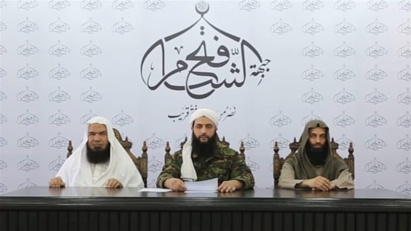 The leader of the Nusra Front, Abu Mohammed al-Joulani, centre, reading the announcement of the creation of Jabhat Fath al-Sham [EPA]