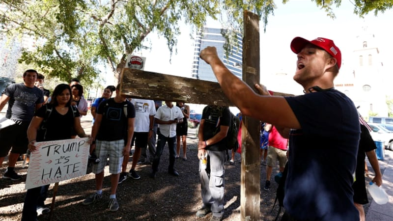 Trump supporters faced protesters outside the Phoenix Convention Center as prepared to speak [Nancy Wiechec/Reuters]