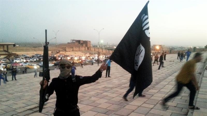 An ISIL fighter holding the group's flag in the Iraqi city of Mosul [File: Stringer/Reuters]