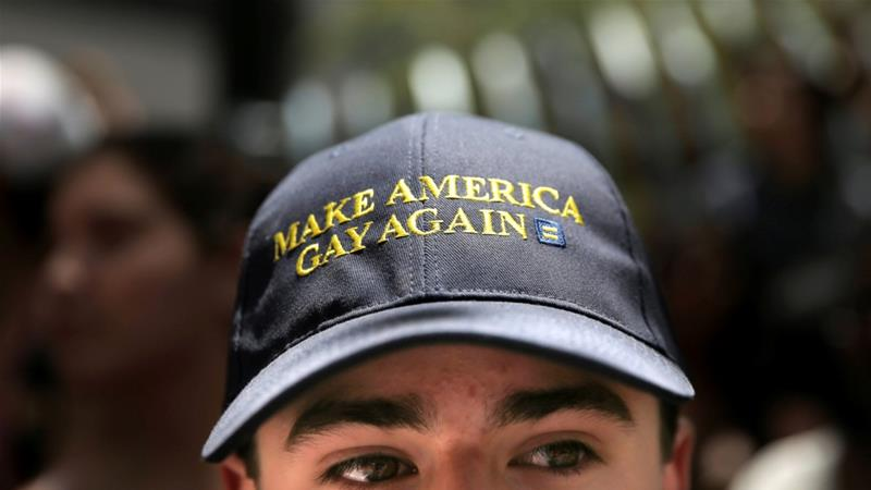 A man wears a hat that says 'Make America Gay Again', a parody of Donald Trump's campaign slogan while watching the San Francisco LGBT Pride Parade in San Francisco [File: Reuters]
