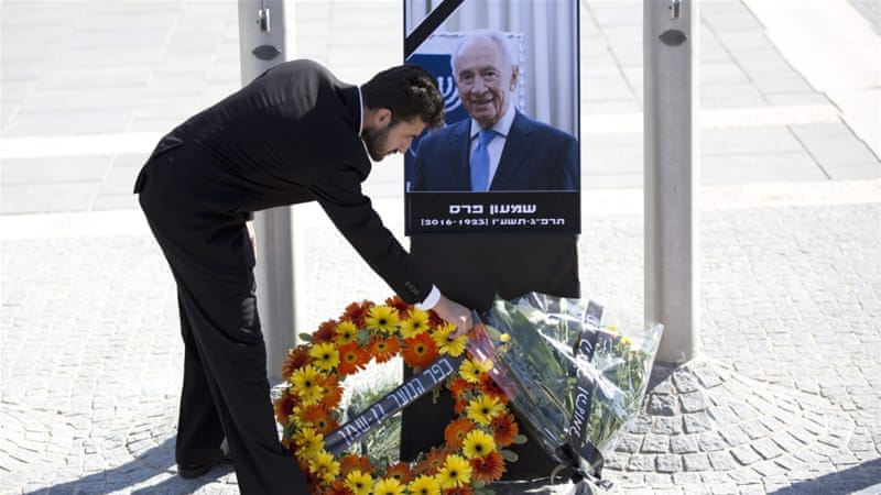 People place flowers on a picture of the late Shimon Peres [EPA]