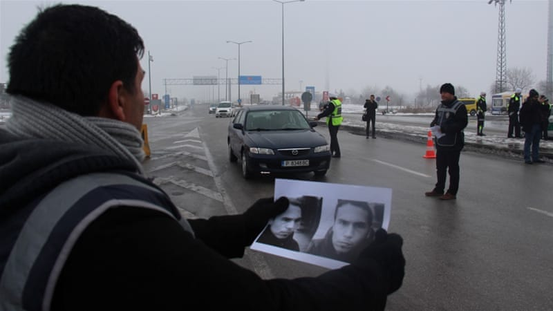 A Turkish policeman holds pictures of the suspected gunman behind the Reina attack [Reuters]