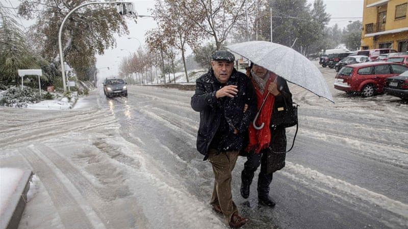 A couple walks through the surprising snow on Nino de Mula in Murcia, eastern Spain [EPA]