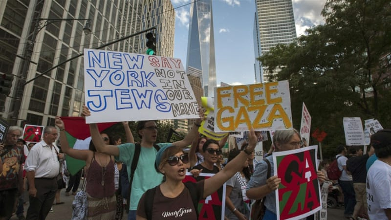 "One World Trade Center is seen in the background as activists hold placards while shouting ""Free, free Palestine"" during a protest march in New York on July 24, 2014 [Reuters]"