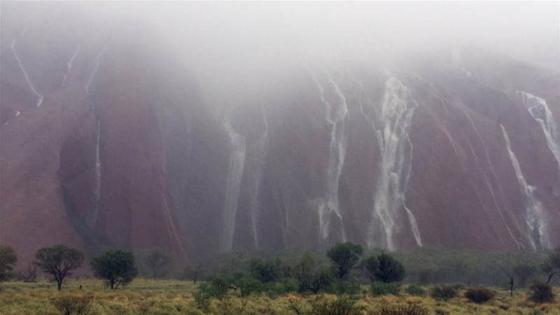 Waterfalls caused by heavy rain run down the side of Australia's famous Uluru rock formation [Reuters]