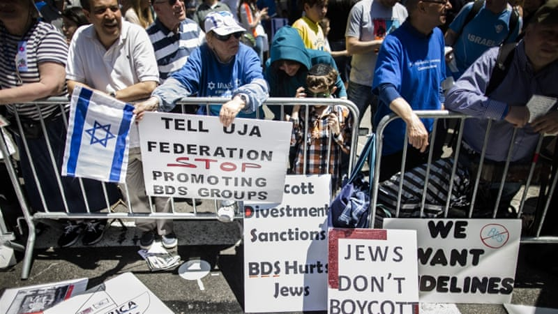 Protesters against the Boycott, Divestment and Sanctions (BDS) movement stand behind a police barricade during the Celebrate Israel Parade in New York [AP]