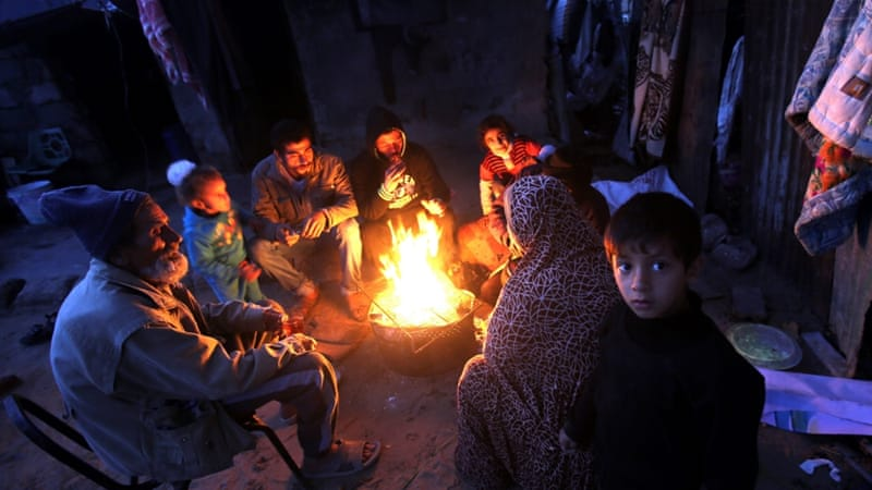 A Palestinian family warm up in front of a fire in cold weather in the Khan Younis refugee camp, southern Gaza Strip [EPA]