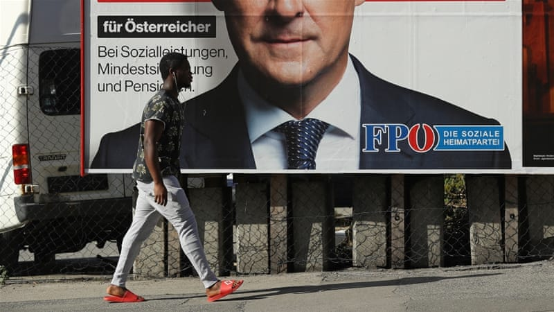 A man of African origin walks past an FPO election campaign billboard [Sean Gallup/Getty Images]