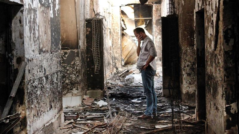 An employee of Doctors Without Borders walks inside the charred remains of the organisation's hospital after it was hit by a US air attack in Kunduz in October 2015 [File: Najim Rahim/AP]