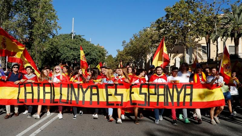 Pro-unionists gather in behind a banner reading 'Catalonia is Spain' during a demonstration in Barcelona on October 8, 2017 [Reuters]