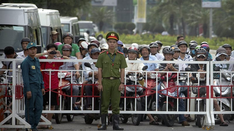 Security officials stop traffic for an official motorcade in Danang on Friday [Mark Schiefelbein/AP]