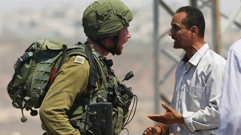 A Palestinian argues with an Israeli soldier during clashes near Qusra in August 2016 [File: Mohamad Torokman/Reuters]