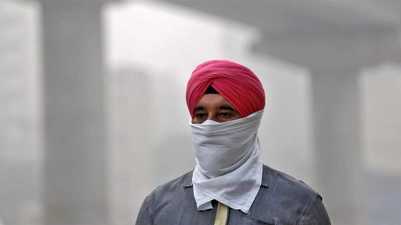 A man covers his face as he walks to work, in Delhi, India, November 7, 2017 [Saumya Khandelwal/Reuters]