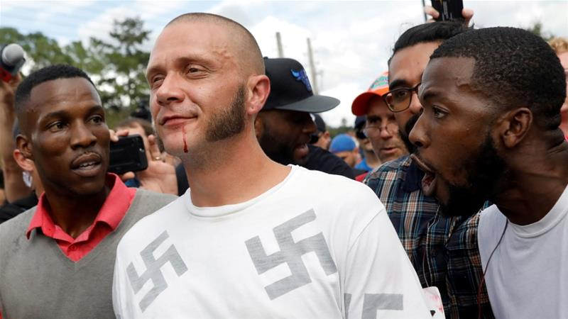 A man walks with a bloody lip as demonstrators yell at him at a far-right demonstration in Florida [File: Shannon Stapleton/Reuters]