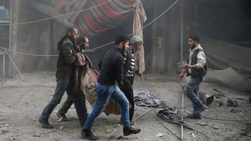 Civilians carry a body in Eastern Ghouta outside the capital Damascus on December 3, 2017 [Bassam Khabieh/Reuters]