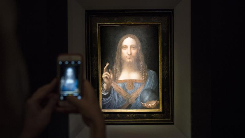 A visitor takes a photo of the Salvator Mundi by Leonardo da Vinci at Christie's New York Auction House [Drew Angerer/Getty Images]