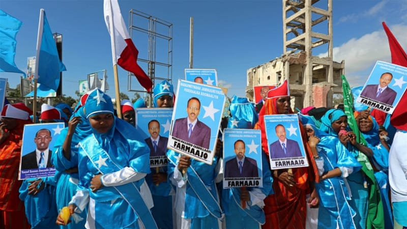 Women carry posters of the newly elected Somalian President Mohamed Abdullahi Mohamed as they celebrate his victory, near the Daljirka Dahson monument in Mogadishu [Feisal Omar/Reuters]
