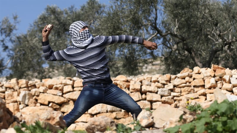 A Palestinian protester hurls stones at Israeli troops during clashes following a protest against a Jewish settlement in the West Bank [Reuters/Mohamad Torokman]