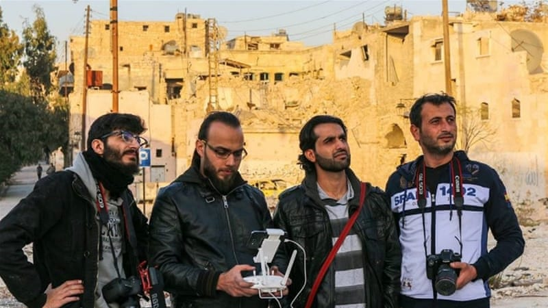 Monther, first left, and Abdalrahman, first right, look up as colleague steers drone in Old Aleppo [Moutaz Khattab/Al Jazeera]