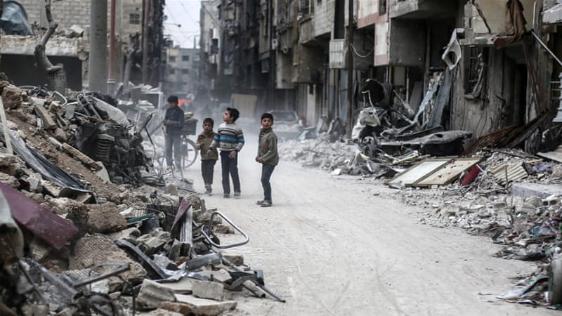 Children stand between the rubble in rebel-held Douma, Syria, February 28 [EPA]