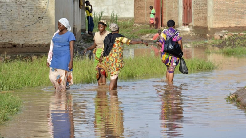 Women walk through muddy floodwaters in Buterere, northwest of Bujumbura [AFP]