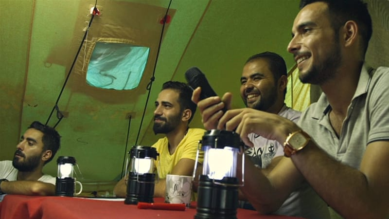 Sameer, Mahmoud, Basil and Mustafa, the four friends behind refugees.tv, sit behind the Refugees Got Talent judges' table in the Oraiokastro refugee camp in Greece [Al Jazeera]