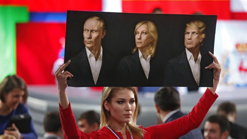 A journalist holds a poster with portraits of Vladimir Putin, Marine Le Pen, and Donald Trump before Putin's annual news conference in Moscow in December 2016 [EPA]