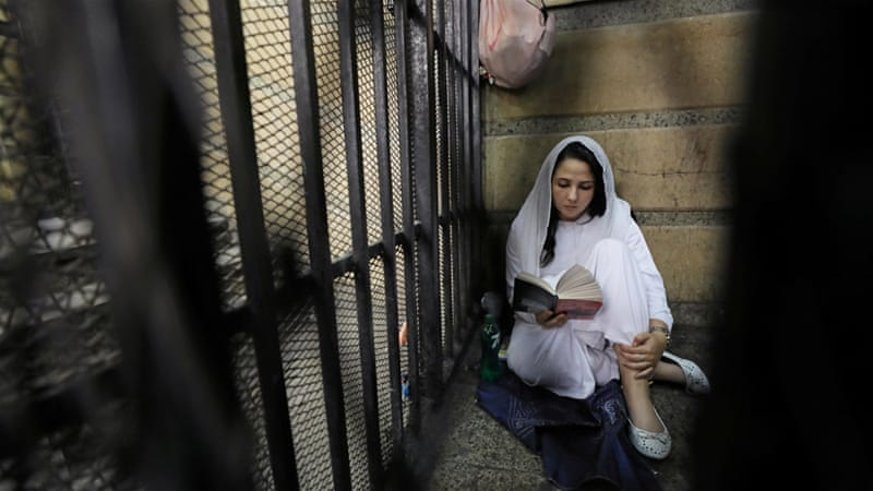 Hijazi seen reading a book inside a cell at a Cairo courthouse [File: Mohamed Abd El Ghany/Reuters]