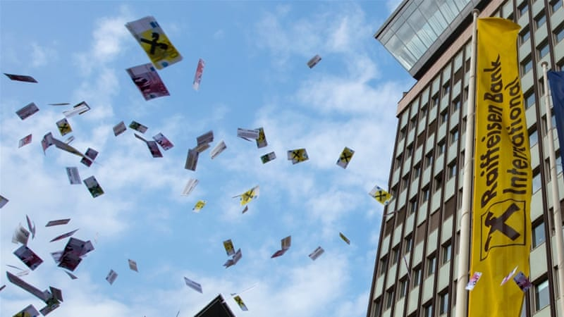 People in Vienna throw fake money in the air during a protest against money laundering after the Panama Papers investigation [File: EPA]