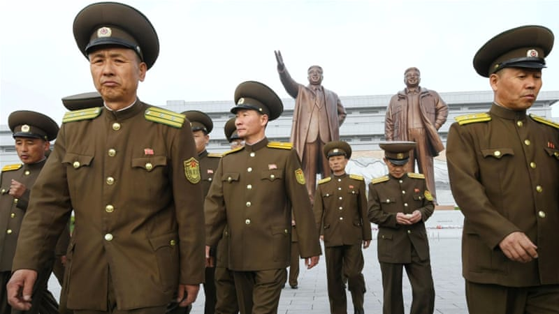North Korean soldiers walk in front of bronze statues of North Korea's late founder Kim Il-sung and late leader Kim Jong-il at Mansudae in Pyongyang [Reuters]