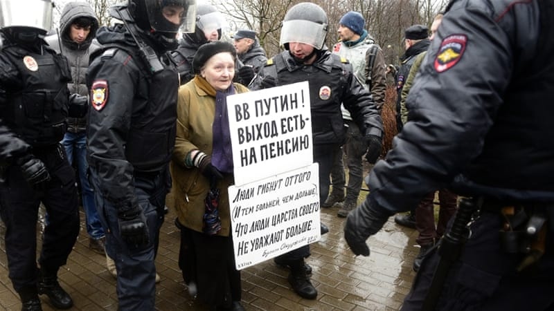 Police detain an elderly activist during an anti-Putin rally in St Petersburg on Saturday [Olga Maltseva/AFP]