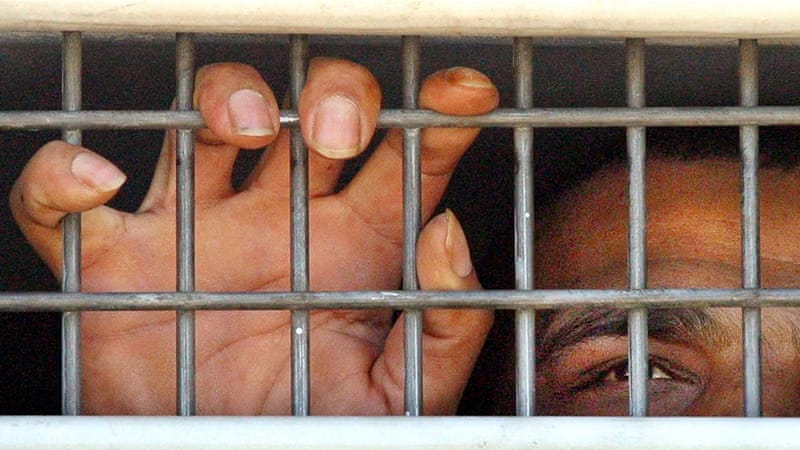 A Palestinian prisoner is seen behind bars as he is brought into the Hadariam prison, north of Tel Aviv [File: Tsafrir Abayov/The Associated Press]