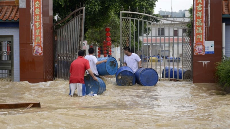 Residents float barrels and belongings through the flooded streets in south China's Gaungzhou province [AFP]