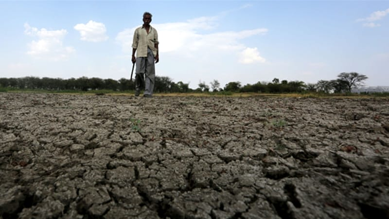 A man walks across a dry river bed in a village near Bhopal in Madhya Pradesh in May 2016 [EPA]